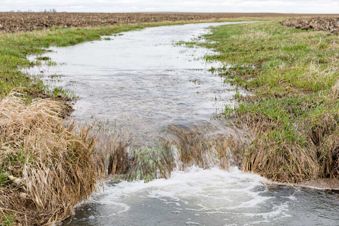 Motion blur of water flowing in farm field waterway to ditch aft